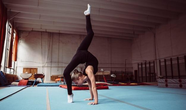 Lang geschoten blonde vrouw die voor gymnastiekkampioenschap traint Gratis Foto