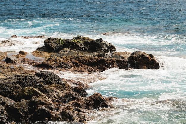 Lang geschoten golvend water op rotsachtige kust Gratis Foto