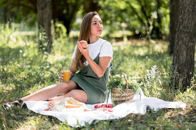 Lang geschoten vrouw die een picknick met gezonde snacks heeft Gratis Foto