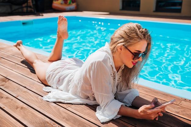 Lang geschotene blondevrouw die haar telefoon controleren Gratis Foto