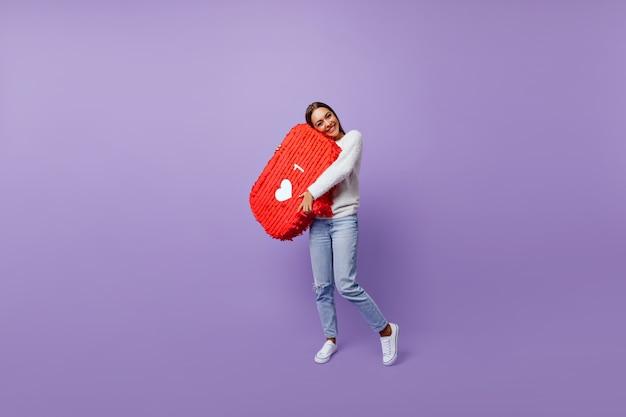 Lang portret van een verfijnd meisje dat geobsedeerd is door sociale netwerken. goed geklede vrouwelijke blogger die zich op paars bevindt Gratis Foto