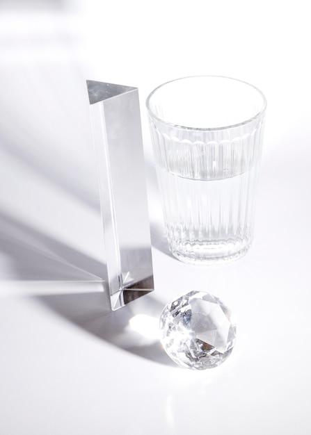 Lang prisma; diamant en glas water in zonlicht met schaduw op witte achtergrond Gratis Foto
