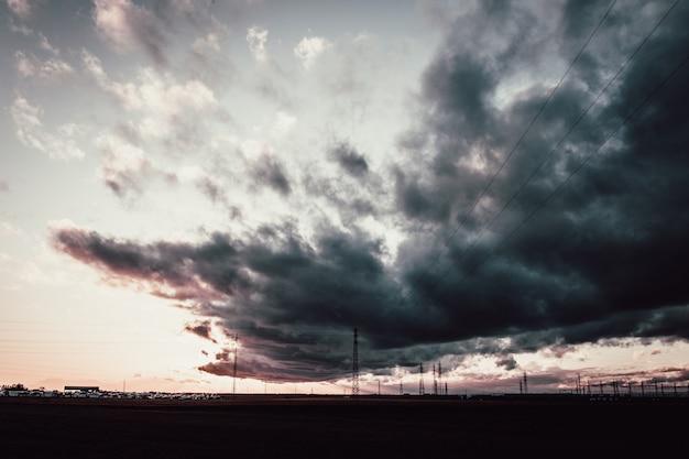 Lang schot van een donkere bewolkte hemel boven antennetorens Gratis Foto