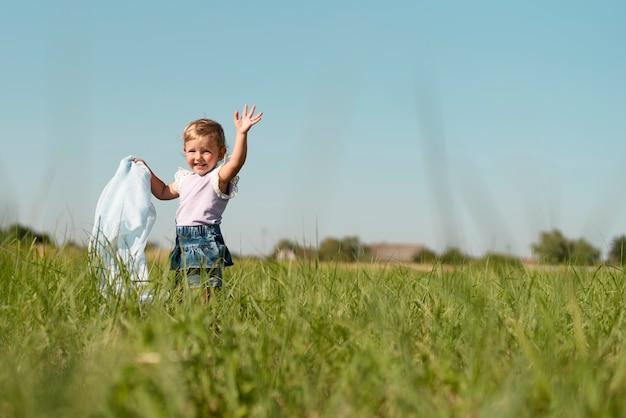 Lang schot van een klein meisje die weg kijken Gratis Foto