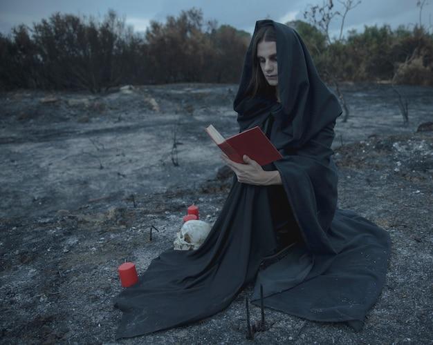 Lang schot van een mannelijke magiër die en een boek zit leest Gratis Foto