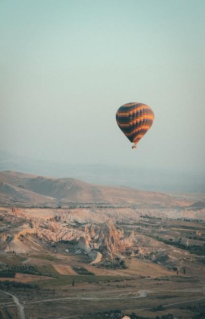 Lang schot van een veelkleurige hete luchtballon die in de hemel hoog boven bergen drijft Gratis Foto