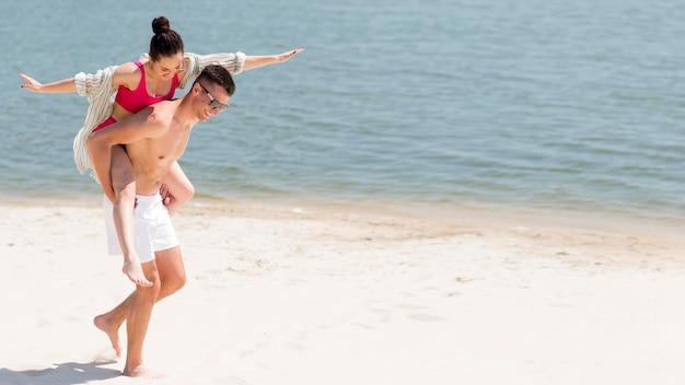 Lang schot van gelukkig paar bij strand Premium Foto
