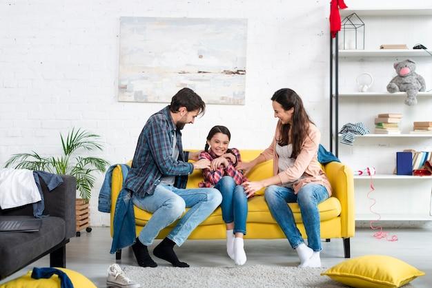 Lang schot van gelukkige familie in woonkamer Gratis Foto