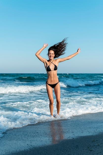 Lang schot van mooi meisje bij strand Gratis Foto