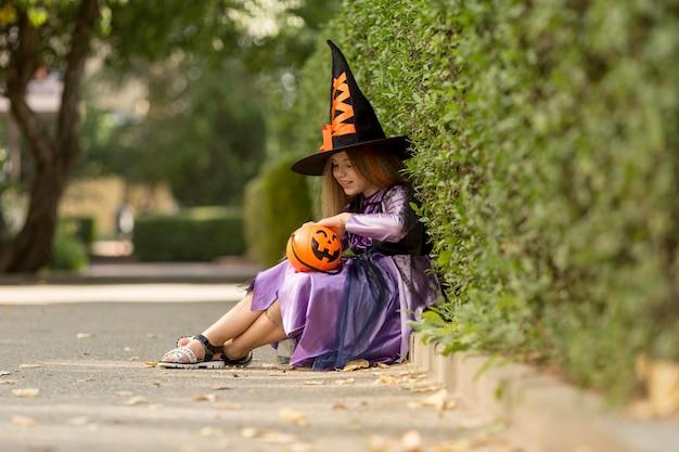 Lang schot van schattig klein meisje met heksenkostuum Gratis Foto