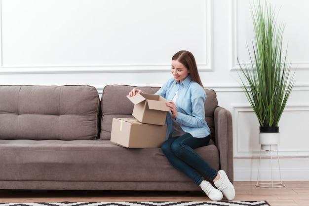 Lang schot van vrouw die een doos opent Gratis Foto