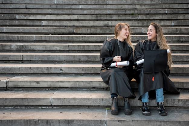 Lange geschotene universiteitsvrienden die op treden lachen Gratis Foto