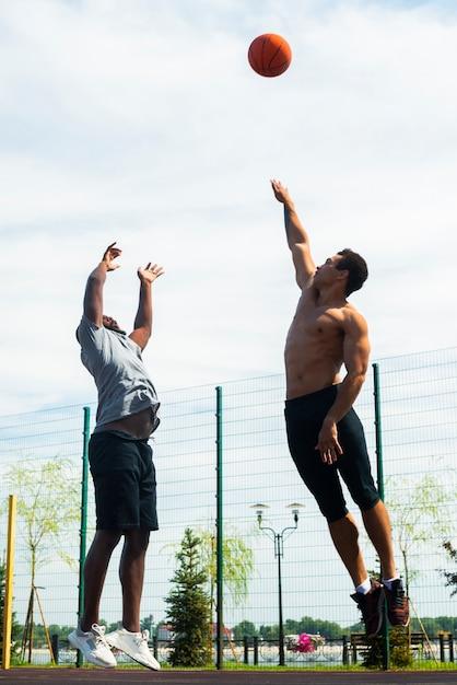 Lange mannen springen op basketbalveld Gratis Foto