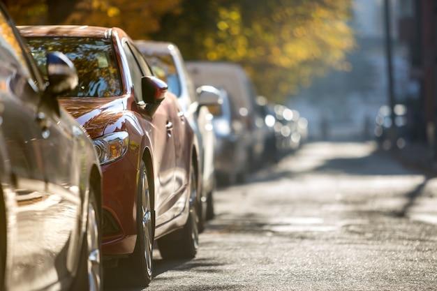 Lange rij van verschillende glanzende auto's en bestelwagens geparkeerd langs lege weg op zonnige herfstdag op wazig groen gouden gebladerte bokeh achtergrond. Premium Foto