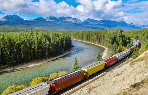 Lange vracht comtainer trein die zich langs boogrivier beweegt in canadese rotsachtige bergen, het nationale park van banff, canadese rotsachtige bergen, canada Premium Foto