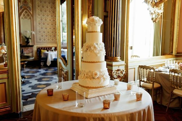 Lange witte moe bruidstaart staat op de ronde tafel Gratis Foto