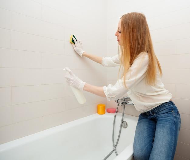 Langharige vrouw schoonmaken tegel met spons in de badkamer Foto ...