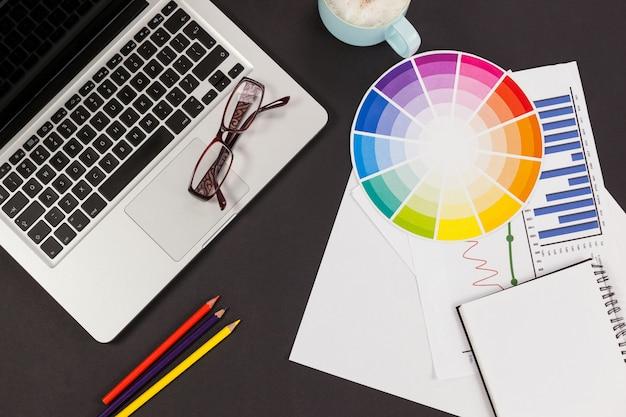 Laptop, bril, kleurpotloden, kleurenschema, koffiekopje, bedrijfsgrafiek en dagboek Premium Foto