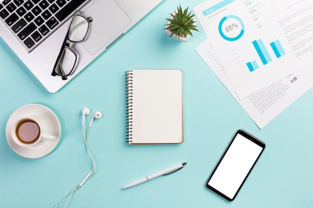 Laptop, brillen, koffiekop, oortelefoons, spiraalvormige blocnote, pen, mobiele telefoon en begrotingsgrafiek op bureau Gratis Foto