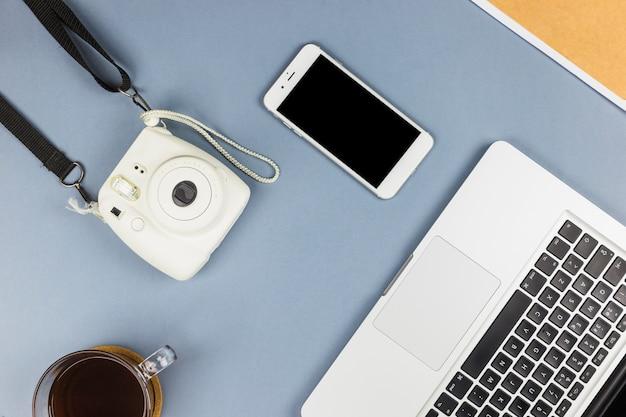 Laptop dichtbij smartphone, camera en kop van drank Gratis Foto