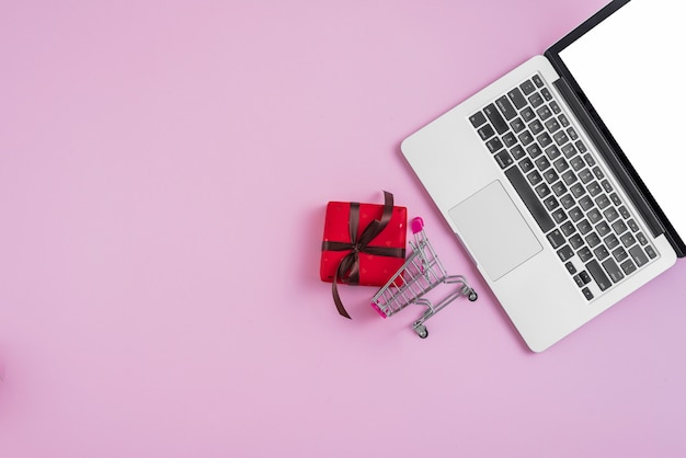 Laptop dichtbij uiterst klein boodschappenwagentje en cadeau Gratis Foto