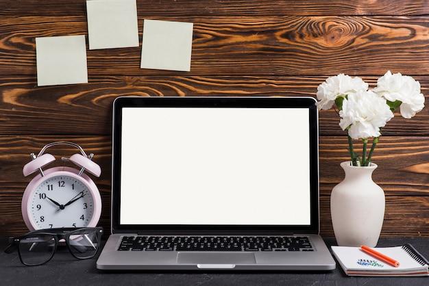 Laptop die wit scherm met vaas toont; potlood en notitieblok op het bureau Gratis Foto