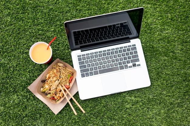 Laptop en chinees voedsel op grasachtergrond Gratis Foto
