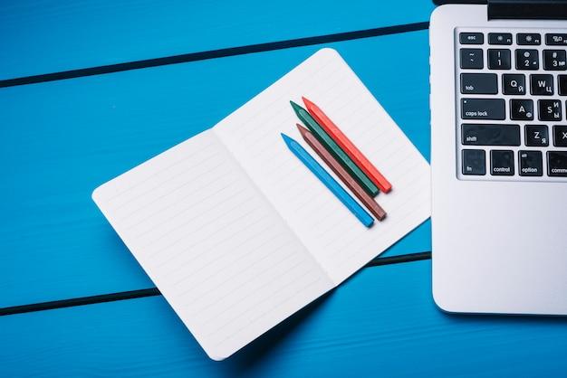 Laptop en notitieboekje op blauw bureau Gratis Foto