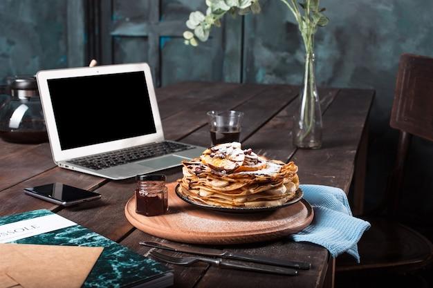 Laptop en pannenkoeken met sap. gezond ontbijt Gratis Foto