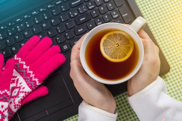Laptop gebruiken in de koude winter - vrouw met handschoenen aan. Premium Foto