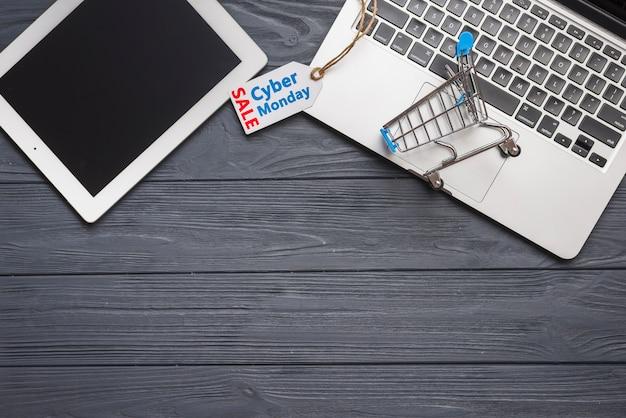 Laptop in de buurt van tag, tablet en supermarktwagen Gratis Foto