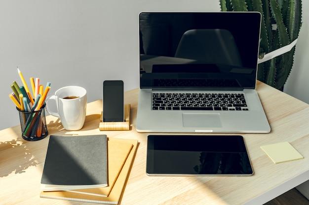 Laptop in een lichte kamer op werktafel met kantoorbenodigdheden Premium Foto