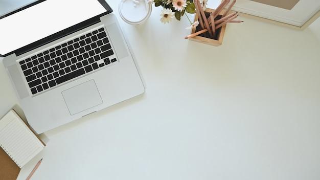 Laptop, koffie, notitieboekjedocument en potlood van het bureaubovenkant met fotokader en bloem op exemplaarruimte. Premium Foto