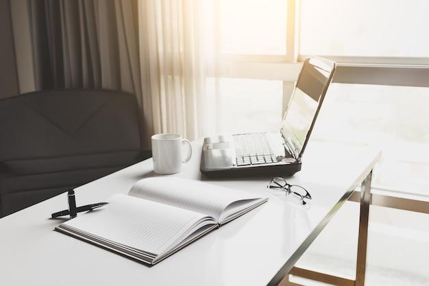 Laptop kopje koffie en dagboek op witte bureau in kantoor foto