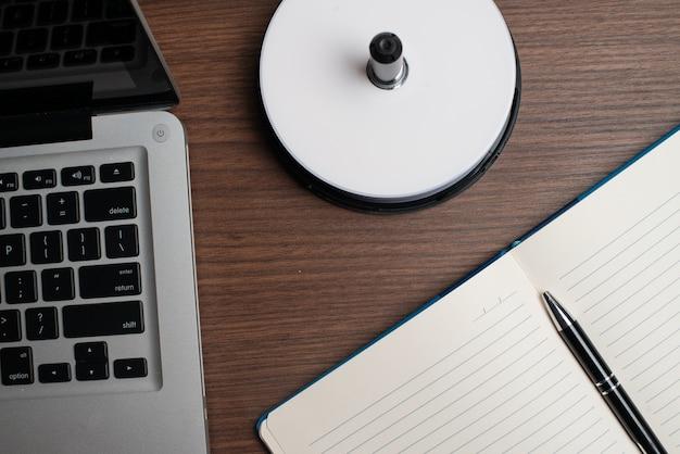 Laptop met cd-schijf en notebook met pen Premium Foto