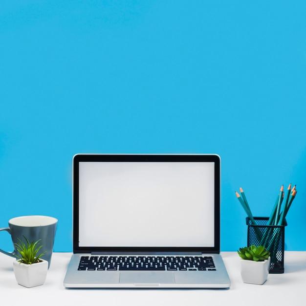 Laptop met koffiekopje op tafel Gratis Foto