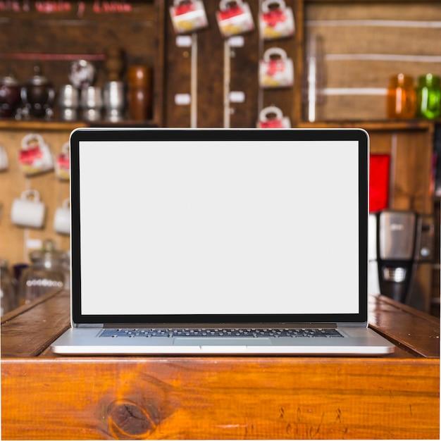 Laptop met leeg wit scherm op tafel in de caf� Gratis Foto