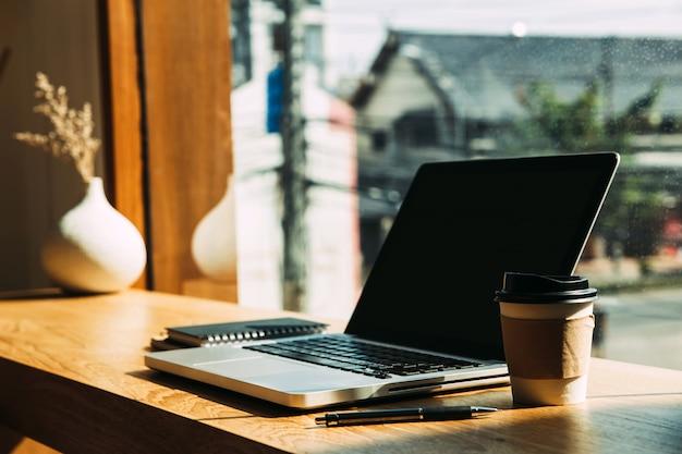 Laptop met papieren koffiemokken, pen op tafel. Premium Foto