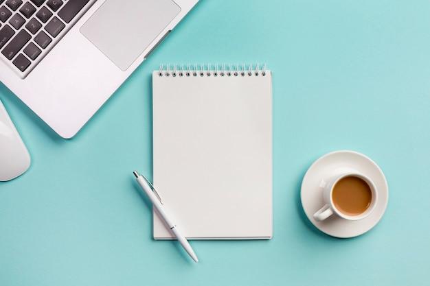 Laptop met spiraalvormige blocnote, muis, koffiekop en pen op blauw bureau Gratis Foto