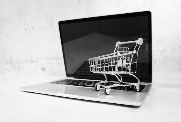 Laptop met winkelwagentje bovenop Gratis Foto