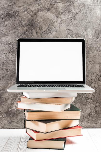 Laptop met wit scherm op de stapel van vintage boeken over de tafel tegen betonnen muur Gratis Foto