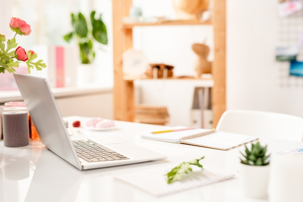 Laptop, notitieblok openen met pen en andere kantoorbenodigdheden op de werkplek van hedendaagse creatieve ontwerper Premium Foto