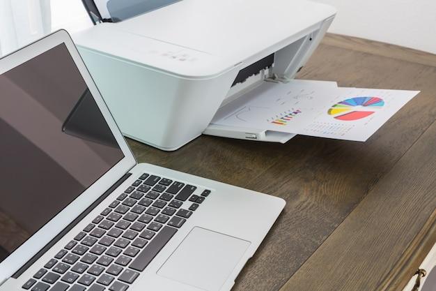 Laptop op een houten tafel met een printer Gratis Foto