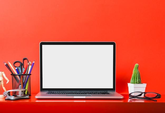 Laptop op rood bureau met kantoorbehoeften en cactusinstallatie Premium Foto