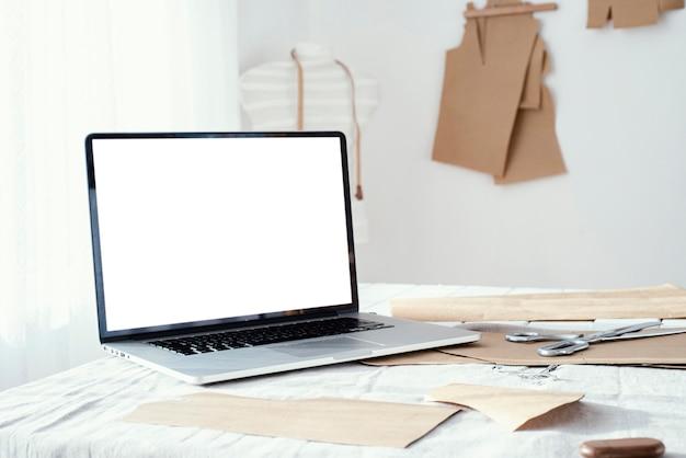 Laptop op tafel in de kleermakerij Gratis Foto