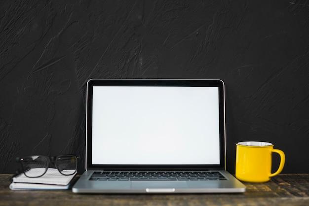 Laptop; schouwspel; gele koffiemok en dagboek op tafel met zwarte getextureerde muur Gratis Foto
