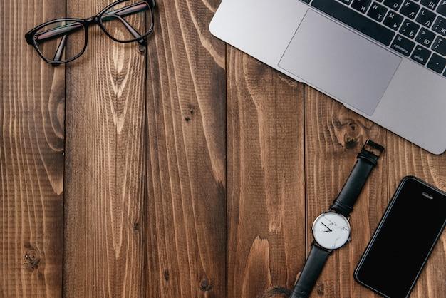 Laptop, smartphone, bril en horloge op houten tafel. Premium Foto