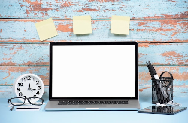 Laptop; wekker; digitale tablet en blanco zelfklevende notities op houten muur Gratis Foto