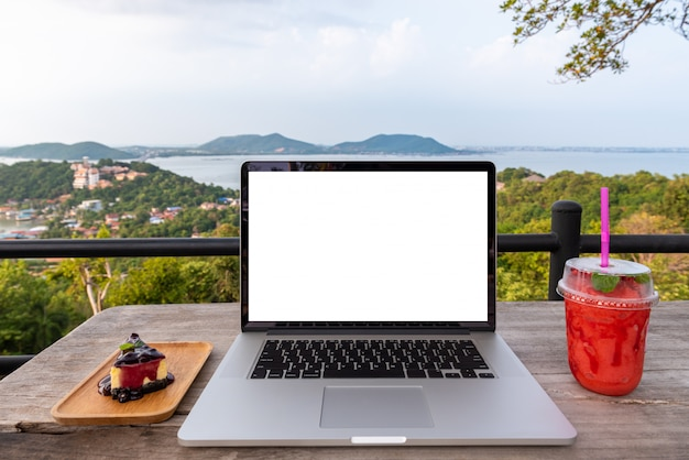 Laptopcomputer met aardbei en cake op houten tafel op het uitzicht op de bergen stad Premium Foto