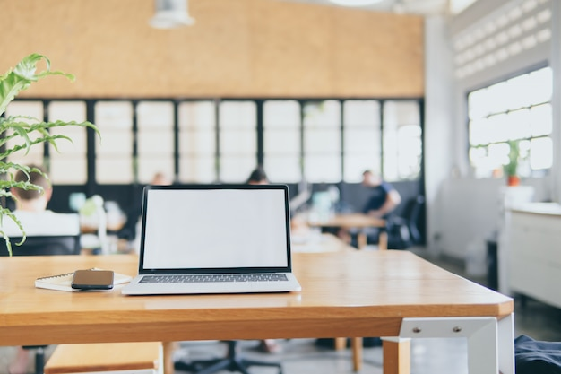 Laptopcomputer op bureau met lege het schermspot op malplaatje. Premium Foto